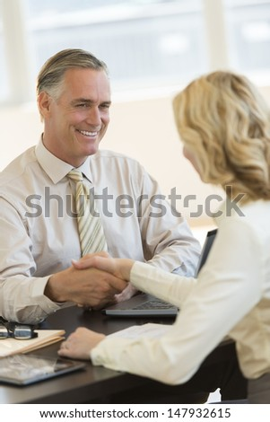 Mature businessman smiling while greeting female colleague at office desk - stock photo