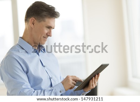 Mature businessman smiling while using digital tablet in office - stock photo