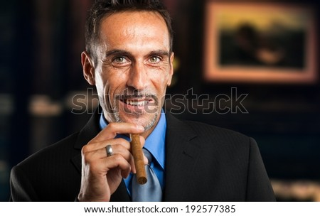 Mature businessman smoking a cigar in a classy room - stock photo