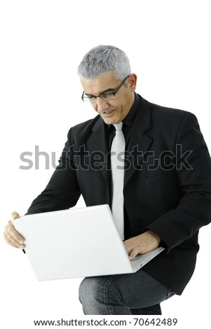 Mature businessman standing, holding laptop computer on his knee. Isolated on white.?