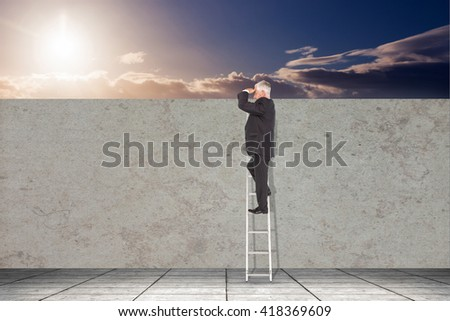 Mature businessman standing on ladder against a beautiful sunset on a beach - stock photo