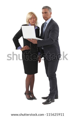 mature businessman standing with laptop and female counterpart - stock photo