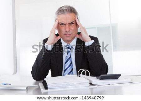 Mature Businessman Suffering From Head Ache At Work - stock photo