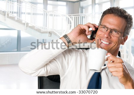 Mature businessman taking a break with a cup of coffee in his modern office - stock photo