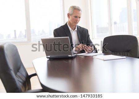 Mature businessman touching smart phone while sitting at desk in office - stock photo