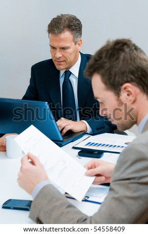 Mature businessman typing on his laptop during a business meeting in office - stock photo