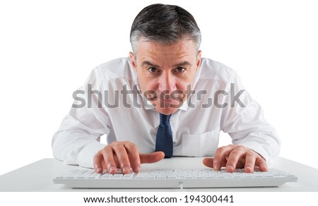 Mature businessman typing on keyboard on white background
