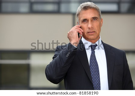 Mature businessman using a cell phone - stock photo