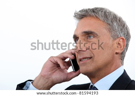 Mature businessman using a cellphone - stock photo