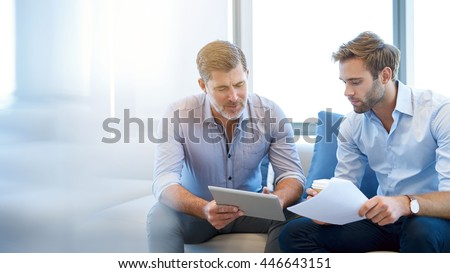 Mature businessman using a digital tablet to discuss information with a younger colleague in a modern business lounge - stock photo