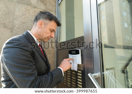 Mature Businessman Using Door Security System On Wall