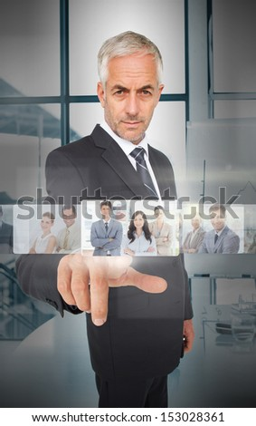 Mature businessman using futuristic interface showing coworkers - stock photo