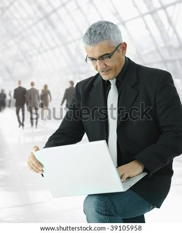 Mature businessman  using laptop computer standing in office hallway, holding the machine on his knee.