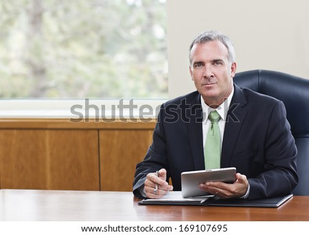 Mature Businessman using tablet computer - stock photo