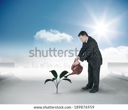Mature businessman using watering can against cityscape on the horizon