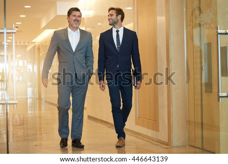 Mature businessman walking with a stylish younger man in a modern office building corridor, talking and smiling pleasantly - stock photo