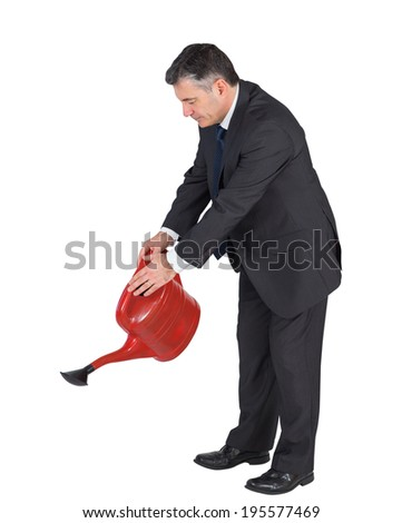 Mature businessman watering with red can on white background