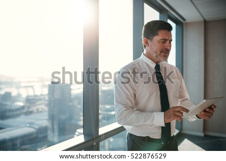 Mature businessman wearing a shirt and tie using a digital tablet while standing at a window in an office overlooking the city