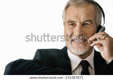 Mature businessman wearing telephone headset, smiling, portrait, cut out