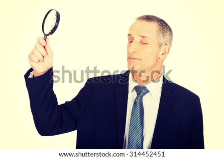 Mature businessman with a magnifying glass.