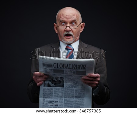 Mature businessman with newspaper expressing amazement
