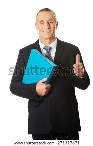 Mature businessman with ok sign holding a binder. - stock photo