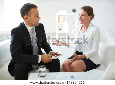Mature businessman with touchpad looking at his colleague while discussing new ideas in office - stock photo