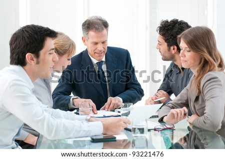 Mature businessman working and discussing with his colleagues at office - stock photo