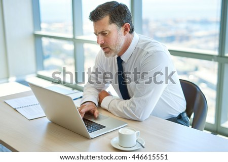 Mature businessman working at this office desk and typing on his laptop, with a serious expression on his face