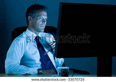 Mature businessman working late at night in his office - stock photo