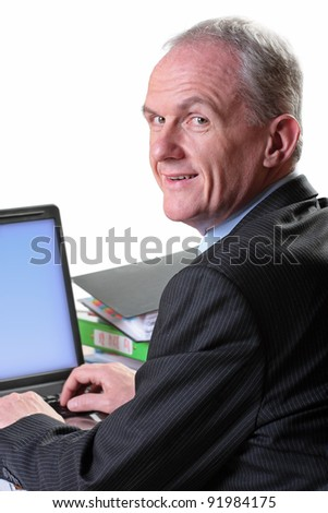 Mature businessman working on a laptop - stock photo