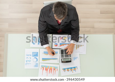 Mature Businessman Working On Calculator For Analyzing Graph On Desk - stock photo
