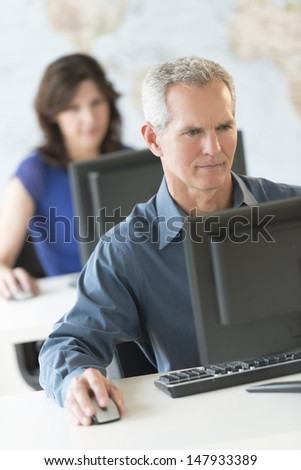 Mature businessman working on computer with female colleague in background at office - stock photo