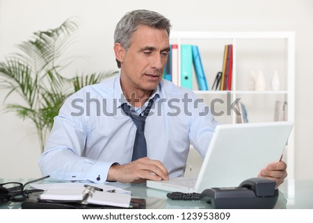 mature businessman working on his desk - stock photo