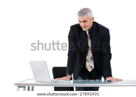 Mature businessman working on laptop computer at desk az office, smiling, isolated on white background.