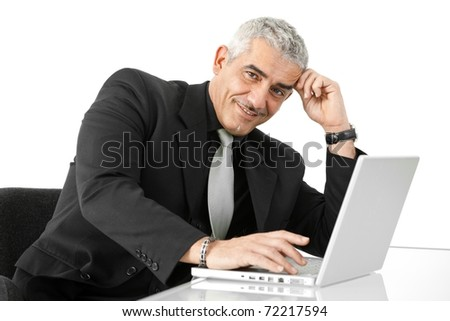 Mature businessman working on laptop computer at office desk, smiling, isolated on white background.?