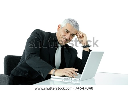 Mature businessman working on laptop computer at office desk, smiling, isolated on white background.? - stock photo