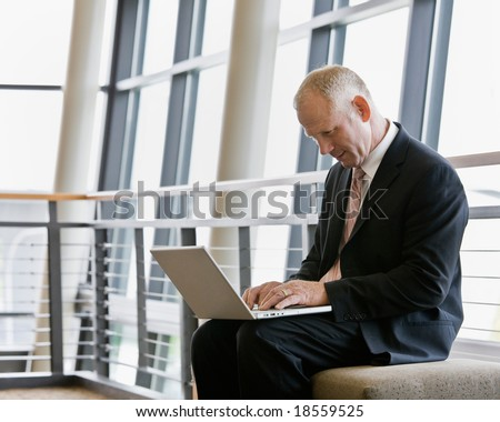 Mature businessman working on laptop in office lobby - stock photo