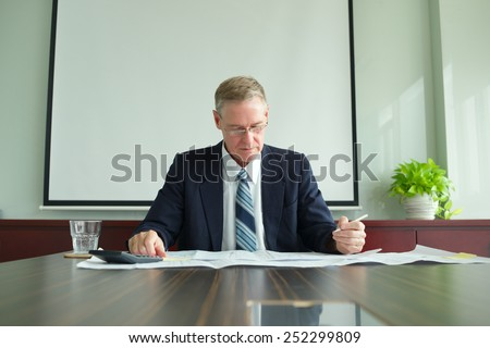 Mature businessman working with blueprints in the office