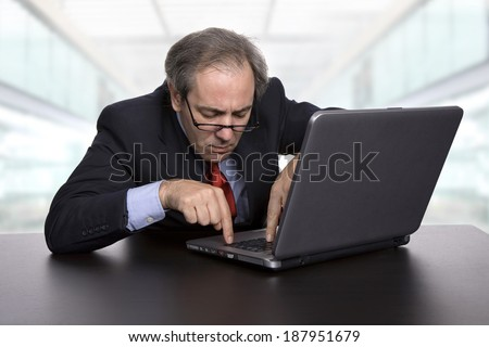 mature businessman working with his laptop, at the office