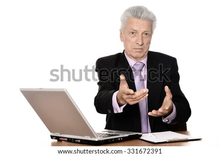 Mature businessman working with laptop on white background