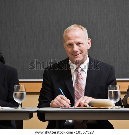 Mature businessman writing notes at table in conference room - stock photo
