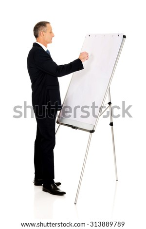 Mature businessman writing on a flipchart