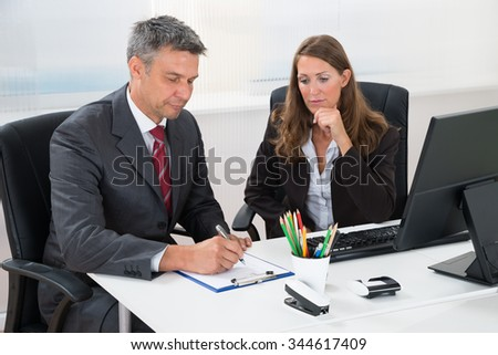Mature Businessman Writing On Clipboard With Female Assistant At Desk In Office - stock photo