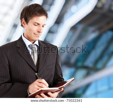Mature businessman writing on his agenda