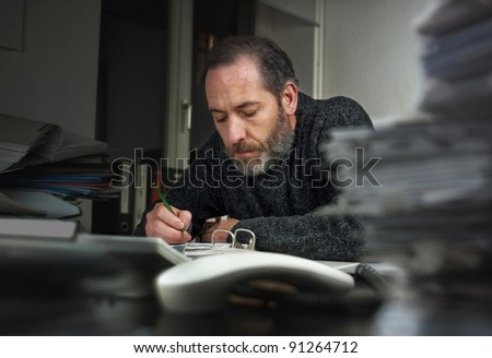 Mature businessman writing on papers at office. Horizontal shot - stock photo