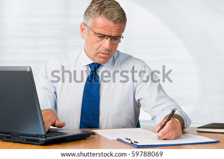 Mature businessman writing on paperwork and working with laptop in his office