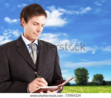 Mature businessman writing something on his agenda outdoor. - stock photo