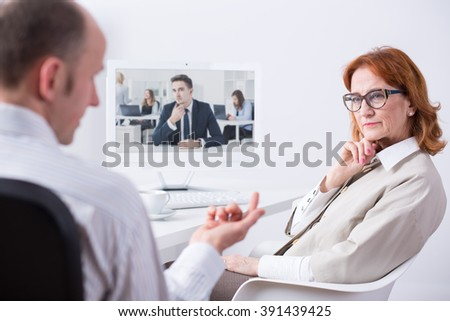 Mature businesspeople sitting beside desk in light office, talking with young businessman via internet