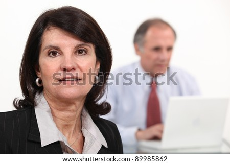 Mature businesswoman and man using a laptop - stock photo